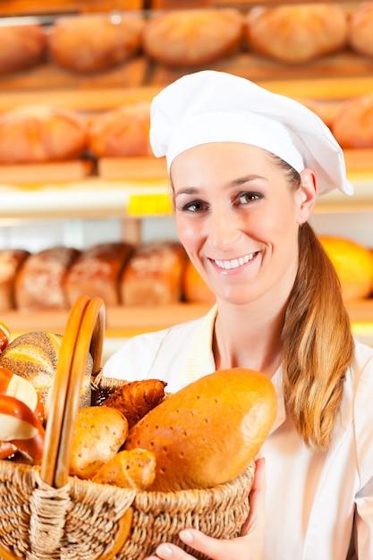 Weiblicher bäcker in der bäckerei, die brot durch korb verkauft Premium Fotos