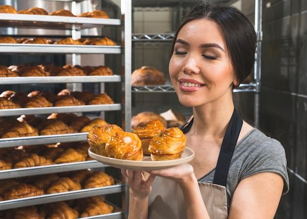 Weiblicher bäcker in der bäckerei, die frischen blätterteig auf platte riecht Kostenlose Fotos