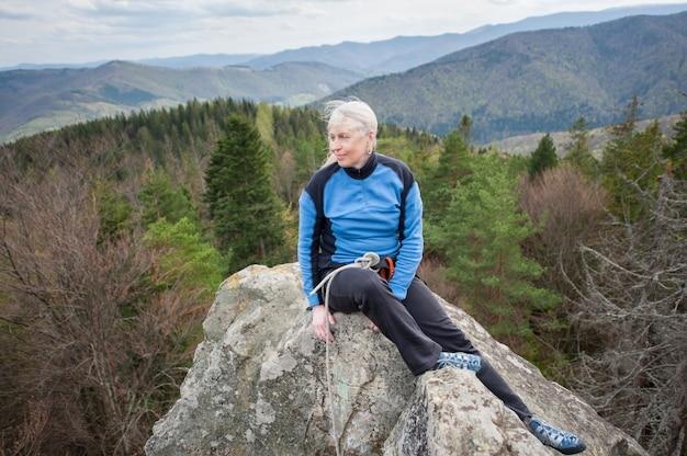 Weiblicher bergsteiger auf der spitze des felsens mit kletternder ausrüstung Premium Fotos