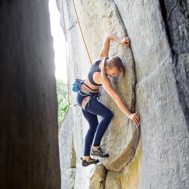 Weiblicher bergsteiger, der mit seil auf einer felsigen wand klettert Premium Fotos