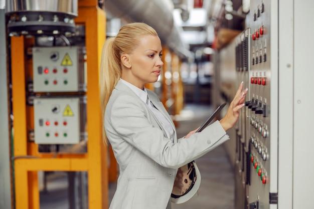 Weiblicher blonder aufseher, der im heizwerk neben armaturenbrett steht, einstellungen anpasst und tablette hält. Premium Fotos