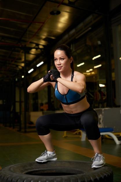 Weiblicher bodybuilder, der auf einem reifen in einer crossfit mitte hockt Kostenlose Fotos