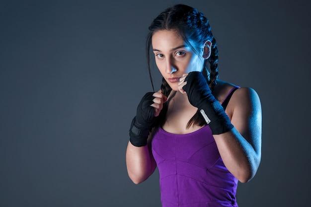 Weiblicher boxer macht einen kampf mit einem schatten, dunkler hintergrund mit platz für text Premium Fotos