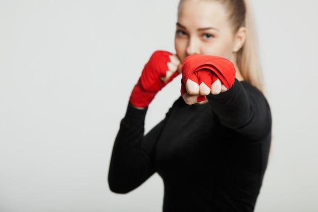 Weiblicher boxer macht einen kampf mit einem schatten, weißer hintergrund mit platz für text Premium Fotos