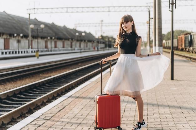 Weiblicher brünetter reisender mit rotem koffer, der auf raiway station geht Premium Fotos
