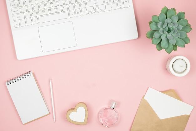 Weiblicher bürodesktop mit bürozubehör auf rosa oberfläche. damenarbeitsbereich mit sukkulenten, kerzen und kosmetika. Premium Fotos