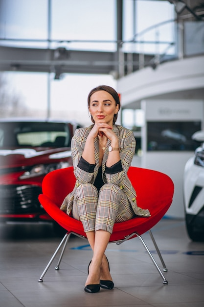 Weiblicher chef an einem auto showrrom, das in einem roten stuhl sitzt Kostenlose Fotos