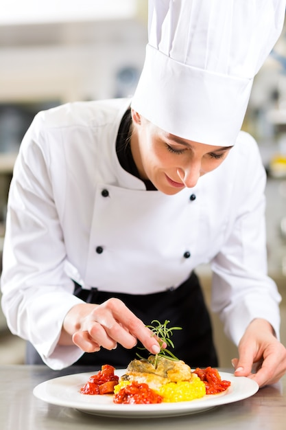 Weiblicher chef beim restaurantküchenkochen Premium Fotos