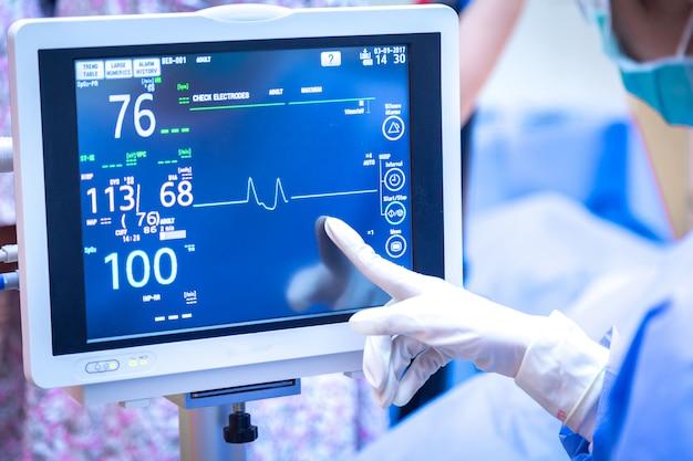 Weiblicher chirurg, der monitor im operationsraum verwendet. Premium Fotos