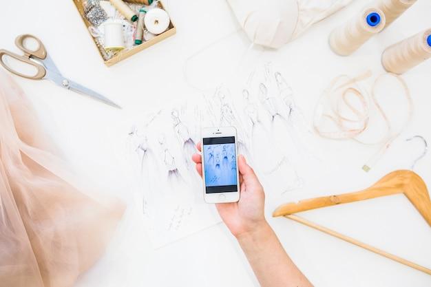 Weiblicher designer, der fotografie der modeskizze auf smartphone macht Kostenlose Fotos