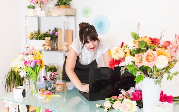 Weiblicher florist, der an laptop mit blumen auf schreibtisch arbeitet Kostenlose Fotos