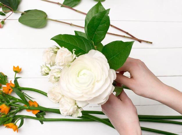 Weiblicher florist, der schönen blumenstrauß am blumenladen macht Kostenlose Fotos