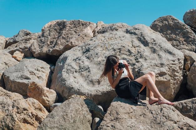 Weiblicher fotograf, der auf dem felsen macht foto mit kamera nahe meer sitzt Kostenlose Fotos