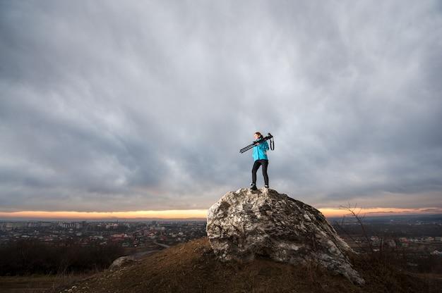 Weiblicher fotograf mit kamera auf stativ auf dem großen felsen Premium Fotos