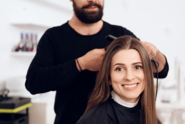 Weiblicher friseur richten braunes haar zur hübschen frau gerade. Premium Fotos