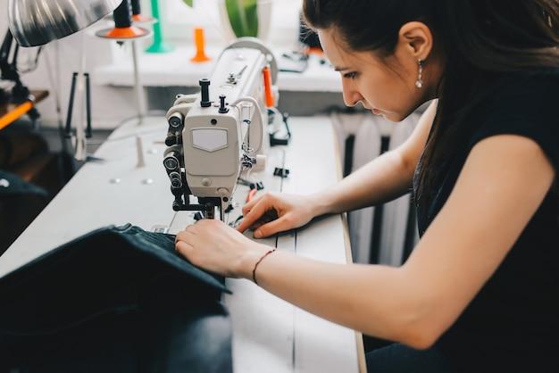 Weiblicher handwerker, der schwarzes leder auf nähmaschine verlegt Kostenlose Fotos