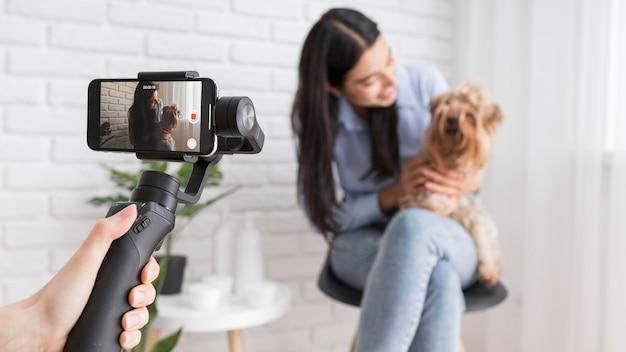 Weiblicher influencer zu hause mit smartphone und hund Premium Fotos