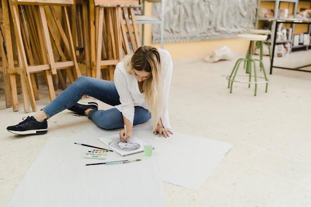 Weiblicher künstler, der auf bodenmalereiskizze auf papier sitzt Kostenlose Fotos