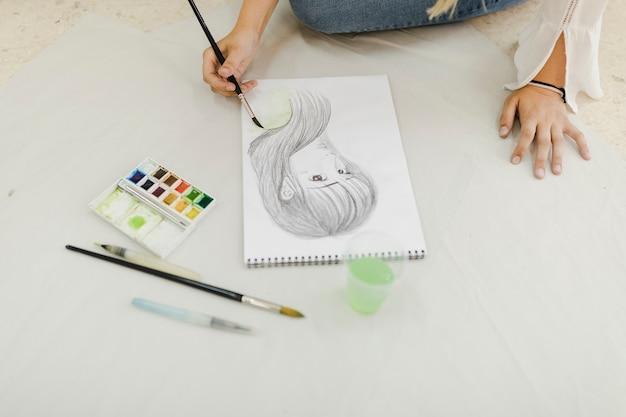 Weiblicher künstler, der auf weiblicher gesichtsskizze malt Kostenlose Fotos