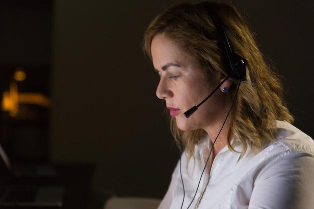 Weiblicher kundenkontaktcenterbetreiber im dunklen büro Kostenlose Fotos