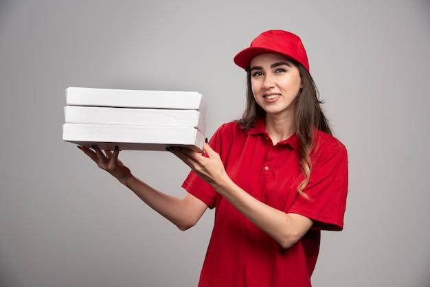 Weiblicher kurier, der pizzaschachteln auf grauer wand hält. Kostenlose Fotos