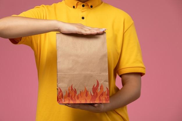 Weiblicher kurier der vorderansicht im gelben einheitlichen gelben umhang, der lieferpaket auf der rosa hintergrunduniform-lieferauftragsarbeit hält Kostenlose Fotos