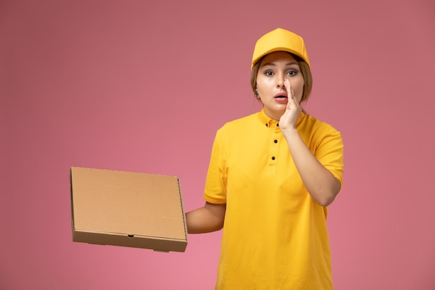 Weiblicher kurier der vorderansicht im gelben uniformgelbumhang, der nahrungsmittelbox hält und auf der weiblichen farbe der rosa schreibtischuniformlieferung flüstert Kostenlose Fotos