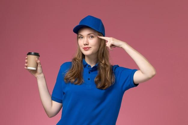 Weiblicher kurier der vorderansicht in der blauen uniform, die braune kaffeetasse mit leichtem lächeln auf hellrosa schreibtischdienstjobuniform-lieferfirma hält Kostenlose Fotos