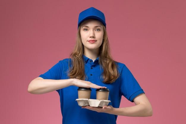 Weiblicher kurier der vorderansicht in der blauen uniform, die braune lieferkaffeetassen auf dem rosa hintergrunddienstuniform-firmenarbeiter hält Kostenlose Fotos