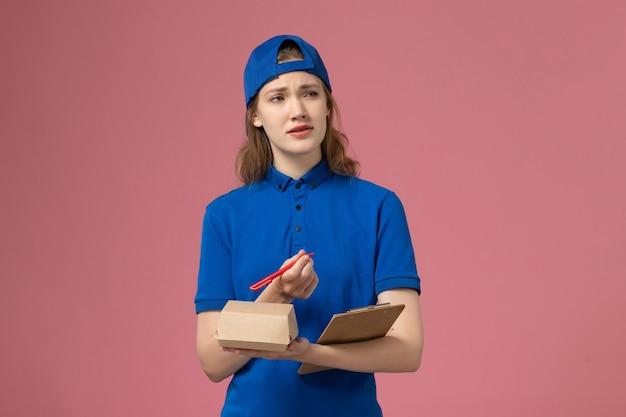 Weiblicher kurier der vorderansicht in der blauen uniform und im umhang, der kleinen notizblock des zustellungsnahrungsmittelpakets hält und auf die rosa wand schreibt, lieferservice-mitarbeiterarbeit Kostenlose Fotos