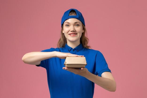 Weiblicher kurier der vorderansicht in der blauen uniform und im umhang, der kleines liefernahrungsmittelpaket auf hellrosa wand hält, lieferuniform-dienstarbeiterangestellter Kostenlose Fotos