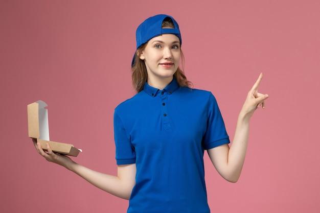 Weiblicher kurier der vorderansicht in der blauen uniform und im umhang, der kleines liefernahrungsmittelpaket auf hellrosa wand hält, lieferuniformdienstmitarbeiterarbeiter Kostenlose Fotos