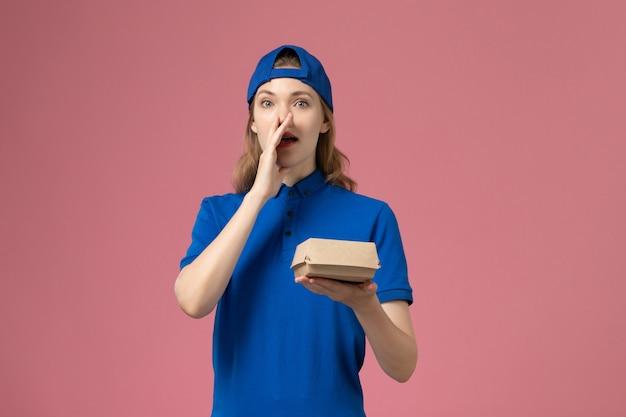Weiblicher kurier der vorderansicht in der blauen uniform und im umhang, der kleines liefernahrungsmittelpaket hält, das an der rosa wand, lieferuniform-servicefirma ruft Kostenlose Fotos