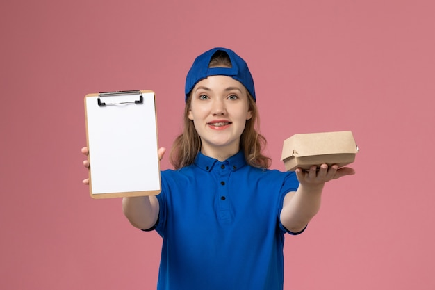 Weiblicher kurier der vorderansicht in der blauen uniform und im umhang, der kleines liefernahrungsmittelpaket und notizblock auf rosa wand, lieferservice-mitarbeiter hält Kostenlose Fotos