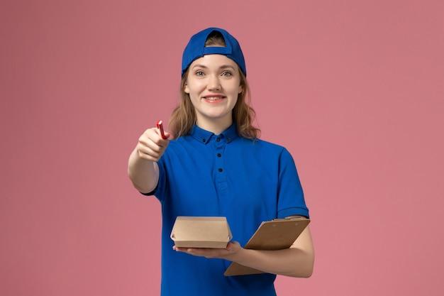 Weiblicher kurier der vorderansicht in der blauen uniform und im umhang, der notizblock des kleinen liefernahrungsmittelpakets hält und auf die rosa wand schreibt, lieferservice-mitarbeiter-arbeiterjob Kostenlose Fotos