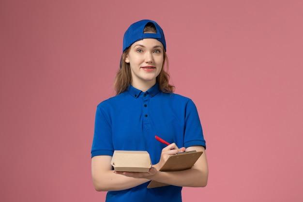 Weiblicher kurier der vorderansicht in der blauen uniform und im umhang, der notizblock des kleinen liefernahrungsmittelpakets hält und auf die rosa wand schreibt, lieferservice-mitarbeiterjob Kostenlose Fotos