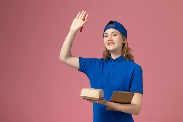 Weiblicher kurier der vorderansicht in der blauen uniform und im umhang, der notizblock des kleinen liefernahrungsmittelpakets hält und auf rosa wand schreibt, joblieferdienstmitarbeiterarbeit Kostenlose Fotos