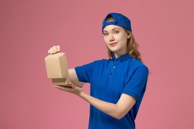 Weiblicher kurier der vorderansicht in der blauen uniform und im umhang, die kleines liefernahrungsmittelpaket auf hellrosa wand halten, lieferuniform-dienstangestellter Kostenlose Fotos