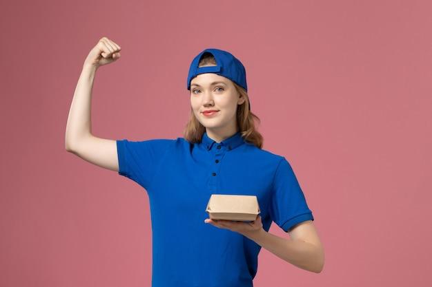 Weiblicher kurier der vorderansicht in der blauen uniform und im umhang, die kleines liefernahrungsmittelpaket halten und auf rosa wand, lieferjobuniform-dienstleistungsunternehmen biegen Kostenlose Fotos