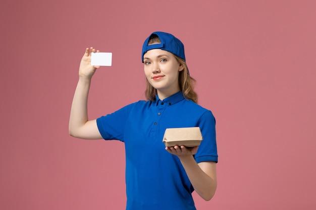 Weiblicher kurier der vorderansicht in der blauen uniform und im umhang, die kleines liefernahrungsmittelpaket mit karte auf rosa wand, lieferservice-mitarbeiter halten Kostenlose Fotos