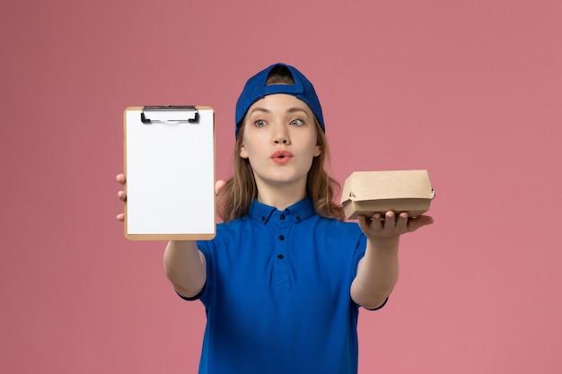 Weiblicher kurier der vorderansicht in der blauen uniform und im umhang, die kleines liefernahrungsmittelpaket und notizblock auf rosa schreibtischlieferdienstmitarbeiter halten Kostenlose Fotos