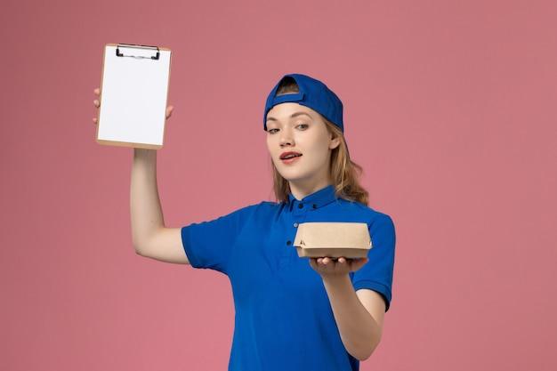 Weiblicher kurier der vorderansicht in der blauen uniform und im umhang, die kleines liefernahrungsmittelpaket und notizblock auf rosa wand halten, arbeiter-zustelldienstmitarbeiter Kostenlose Fotos