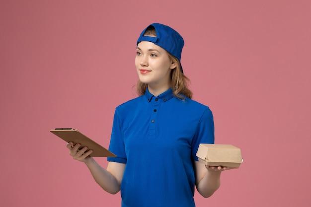 Weiblicher kurier der vorderansicht in der blauen uniform und im umhang, die kleines liefernahrungsmittelpaket und notizblock auf rosa wand halten, lieferarbeitsdienstmitarbeiter Kostenlose Fotos
