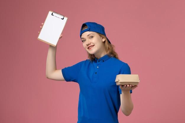 Weiblicher kurier der vorderansicht in der blauen uniform und im umhang, die kleines liefernahrungsmittelpaket und notizblock auf rosa wand halten, lieferservice-mitarbeiterarbeiter Kostenlose Fotos