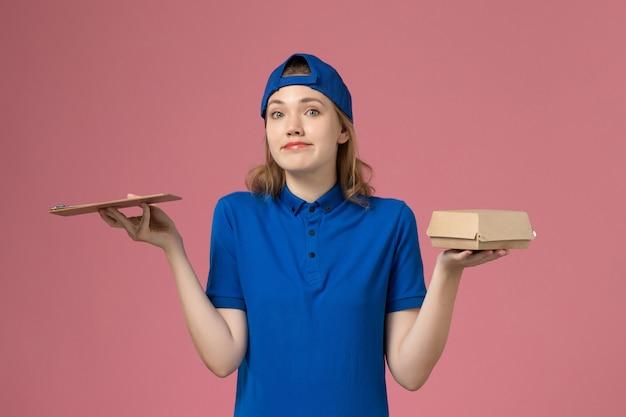 Weiblicher kurier der vorderansicht in der blauen uniform und im umhang, die kleines liefernahrungsmittelpaket und notizblock auf rosa wand halten, lieferservice-mitarbeiterarbeitsjob Kostenlose Fotos