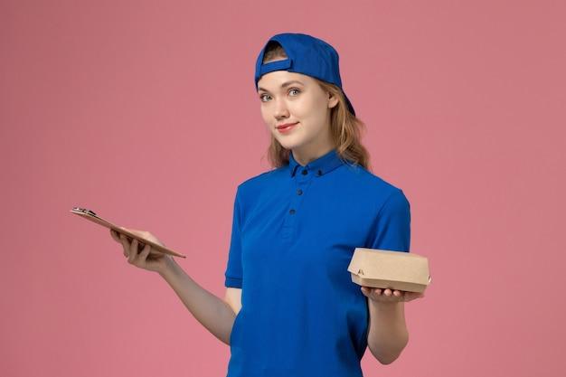 Weiblicher kurier der vorderansicht in der blauen uniform und im umhang, die kleines liefernahrungsmittelpaket und notizblock auf rosa wand halten, lieferservicejobangestellter Kostenlose Fotos