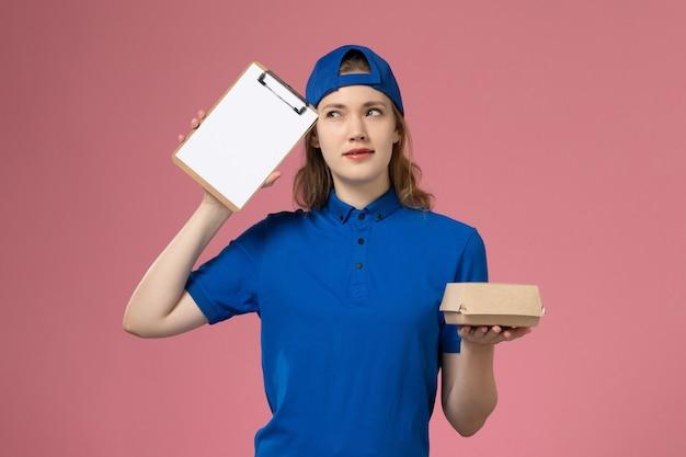 Weiblicher kurier der vorderansicht in der blauen uniform und im umhang, die kleines liefernahrungsmittelpaket und notizblock denken, der an die rosa wand denkt, lieferservice-mitarbeiter Kostenlose Fotos