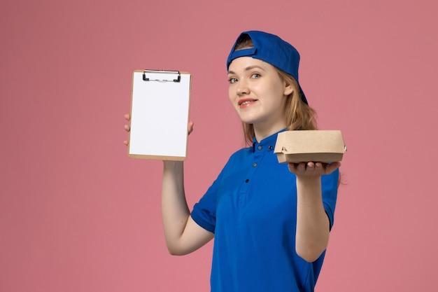 Weiblicher kurier der vorderansicht in der blauen uniform und im umhang, die kleines liefernahrungsmittelpaket und notizblock halten, die auf rosa wand lächeln, lieferservice-mitarbeiter Kostenlose Fotos