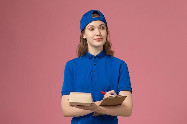 Weiblicher kurier der vorderansicht in der blauen uniform und im umhang, die kleines liefernahrungsmittelpaket und notizblockschreiben auf rosa wand, lieferservice-mitarbeiter halten Kostenlose Fotos