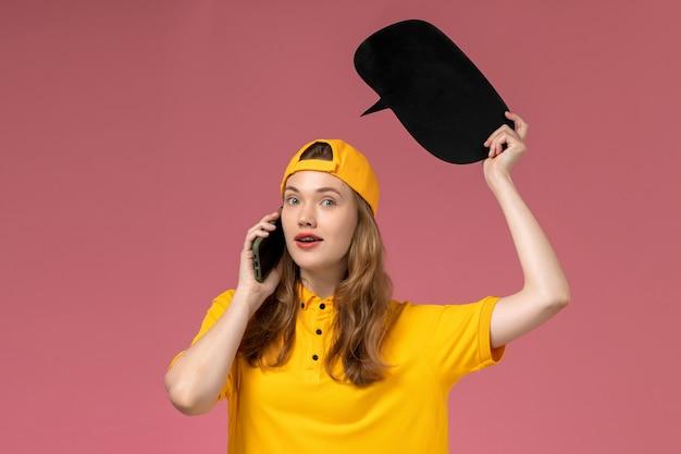 Weiblicher kurier der vorderansicht in der gelben uniform und im umhang, die schwarzes zeichen halten und am telefon auf der rosa wandfirma-dienstarbeiter-lieferuniform sprechen Kostenlose Fotos